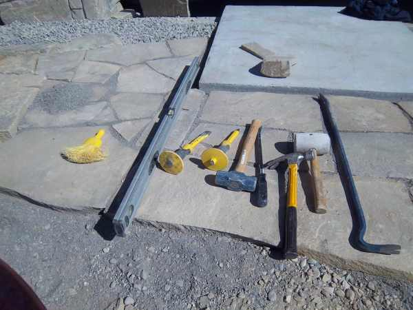 Tools for building a flagstone walkway. Whisk broom, 4 ft. level, 2 stone chisels, a 3 lb sledge hammer, a pry bar, a claw hammer, a rubber mallet (dead blow hammer) and a large pry bar.