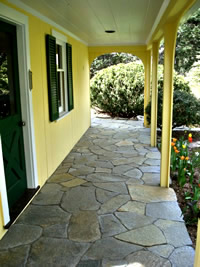 Flagstone porch patio bordered with a garden bed in front leads out to the side yard.