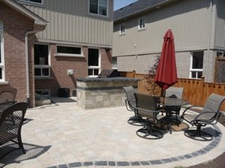 A large nicely shaped patio area with an outdoor kitchen in a typical