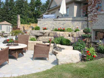 A patio with a firepit is complimented with a wall built out of very large stones.