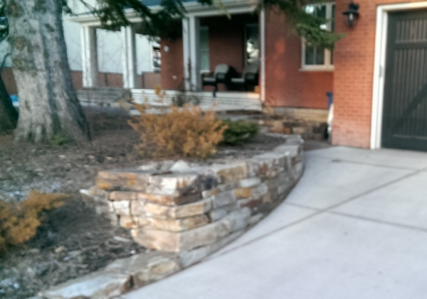 A mixed colour dry stacked stone wall makes a great addition to the front of this home.