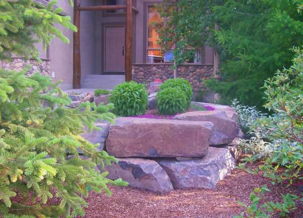 A large block stone retaining wall extends the entryway to include a small garden bed in this front yard.