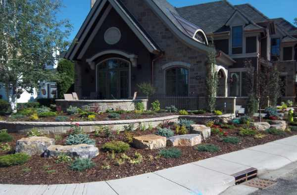 Beautiful corner lot landscaping with formal stone walls are interplanted with a shrub and mulch rock garden.