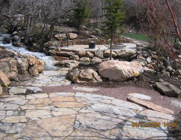 Two patios are connected by a flagstone walkway and large boulders placed in the stream.