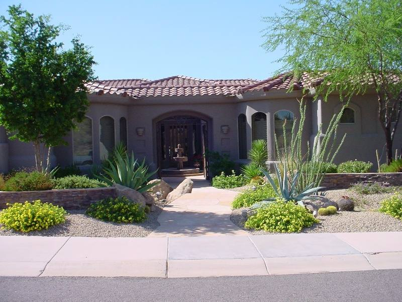 A well balanced front yard design with stone walls and shrubs welcome visitors to a beautiful courtyard entrance with a fountain.