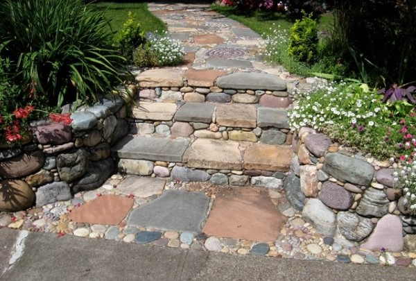 Mixed stone steps with small garden beds on either side lead to up to a beautiful mosaic stone walkway.