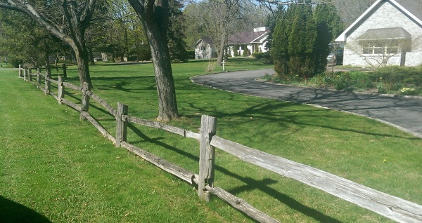 This simple wooden fence crossing multiple properties gives a country feel in an older section of a small town.