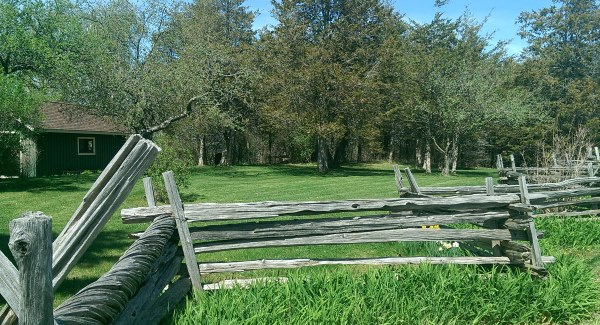 This rustic wooden split rail fence fits right in on this acreage country property.