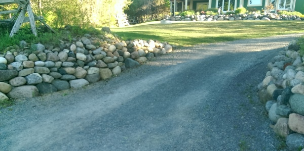 Simple boulder walls line the entrance to this long driveway,  Boulders are an easy way to deal with slopes.