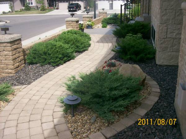 A manufactured brick walkway leading from the front of the house around to the backyard with nice gentle curves.