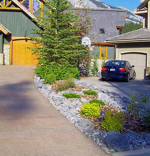 Driveway landscaping between two neighbors with a small slope can be challenging. Instead of building a small retaining wall and separating the properties, try simple rock garden ideas like this.