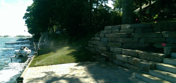 A large block stone retaining wall is used to deal with a steep slope down to the lower patio area and the dock on this cottage property.