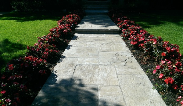 A cut flagstone walkway is a formal way to dress up a front entrance. Spaced plantings provide repetition and a nice rhythm to the walkway.