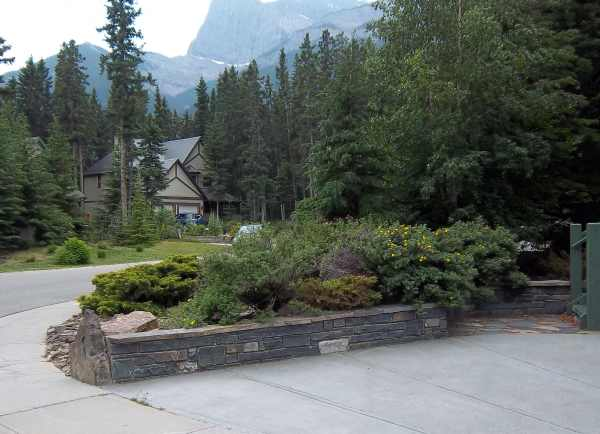 This beautiful low stone retaining wall is a classy way to border a driveway.