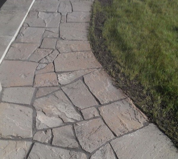 A Dry Laid Flagstone Walkway With 1 2 Inch Gaps Wraps Around The Back Of