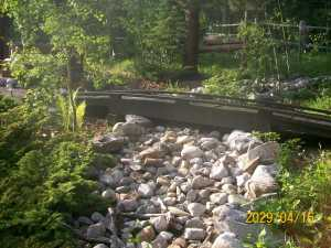 Dry river bed with footbridge in backyard.