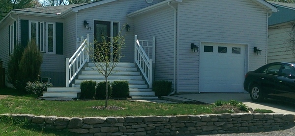 A low fieldstone wall is a great way to dress up a home with a sloping front yard. You can tell by the way these stones were so tightly fitted that it was built with great skill.