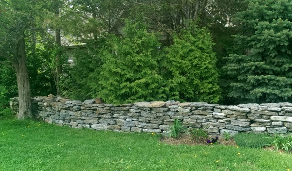 A roughly built fieldstone wall adds character to this private country home.