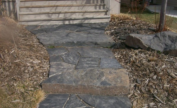A rustic dry laid flagstone walkway welcomes people to this modern home in the city. Instead of sloping a walkway, incorporate a few stone slab steps as seen in this picture.