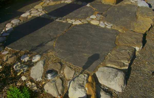 A small seating area in this backyard has a simple base of flagstone with river rock.