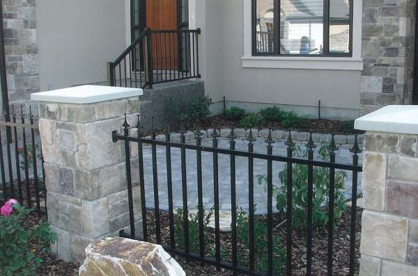 A small brick courtyard enclosed with stone pillars and wrought iron fencing gives a formal look.