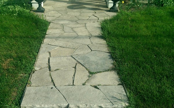 A short flagstone walkway leads to a small patio opening at the front door.