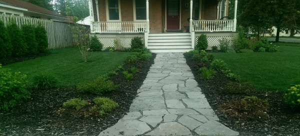 A simple flagstone walkway lined with mulch and perennials creates some interest in this front yard.