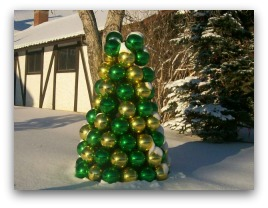 A small tree made out of ornamental Christmas balls stands prominent in this snowy winter scene.