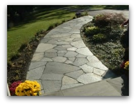 An attractive flagstone walkway with a nice gentle curve from the house to the driveway. Notice the width is wide enough for two people to