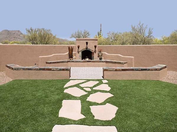 A natural flagstone walkway set in the lawn leads to an outdoor fireplace area.
