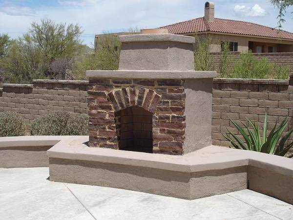 Outdoor desert backyard fireplace combining brickwork into the front face for interest.