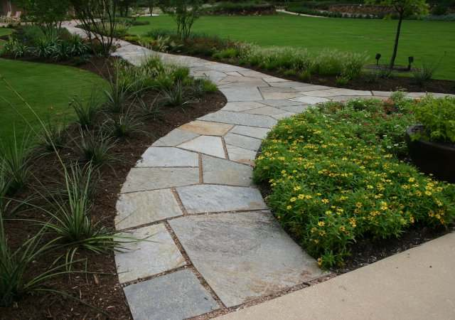 Formal cut stone split arched walkway that wraps around a nice perennial bed.