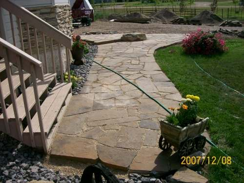 A country property with a flagstone walkway leading up to the front door.