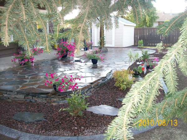 A low two-tiered flagstone patio wraps around the back of this house to the side yard.