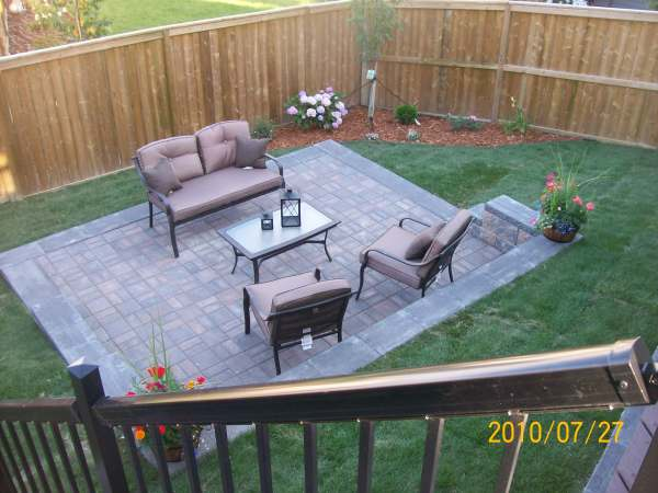Formal Manufactured Brick Patio Recessed Into A Slope In A Small Backyard.