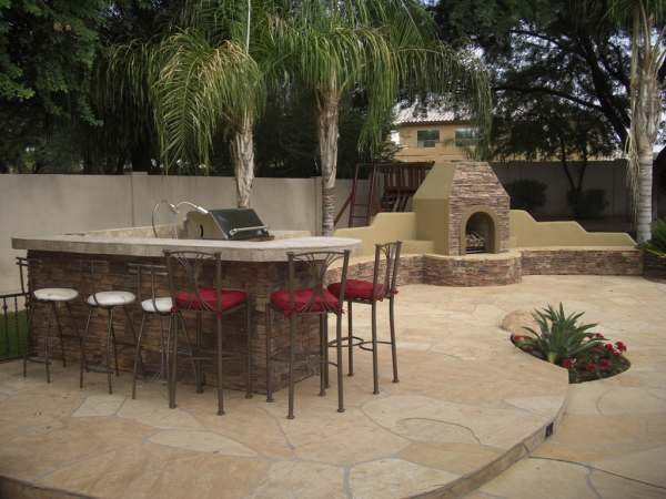 A flagstone patio creates a nice floor for this outdoor kitchen area and fireplace.