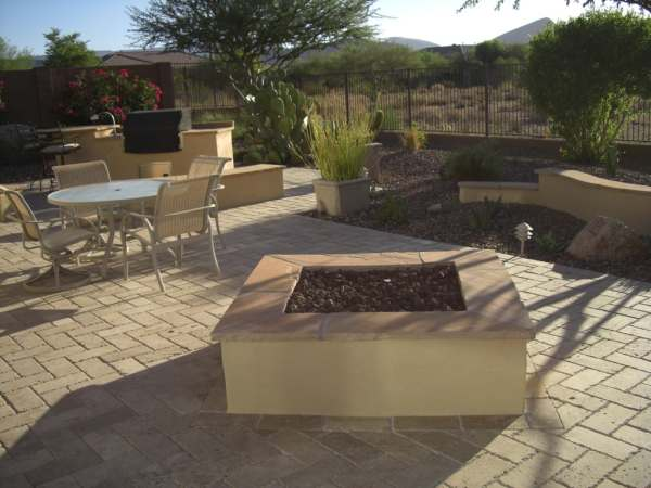 A desert backyard with a large manufactured brick floor connecting the outdoor kitchen, patio, and firepit.