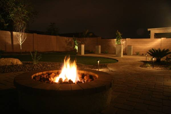 A formal yard is well lit to accent the walkways and trees.