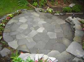A great overhead shot of a flagstone patio showing the back wall and front garden bed.
