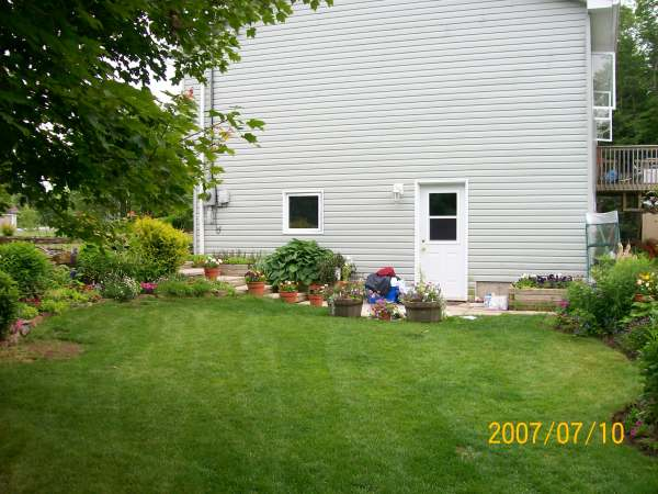 Having a lawn bordered by flower beds, gives this yard colour and interest in every direction.