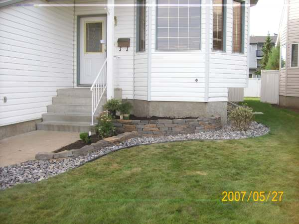A small front garden bed made with natural stone dresses up the front yard while hiding the concrete foundation.