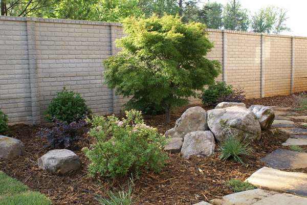 A bed with small shrubs and rocks complimenting the main feature that stands tall in the center.