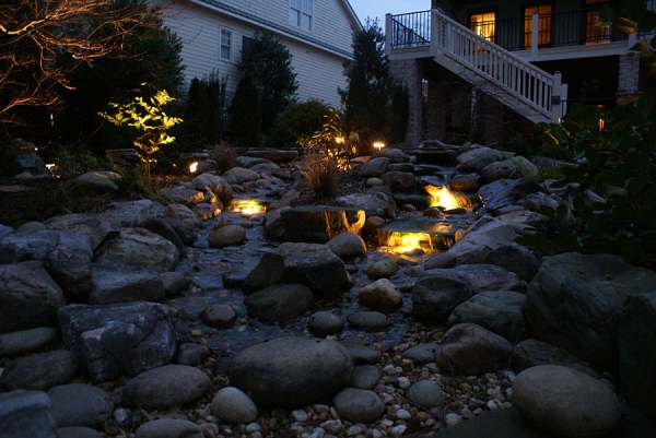 This pondless water feature looks like it came right out of nature with a split stream and a center island planting.