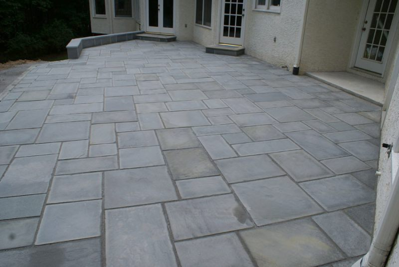 A Large Formal Patio With Cut Stone In A Random Pattern.