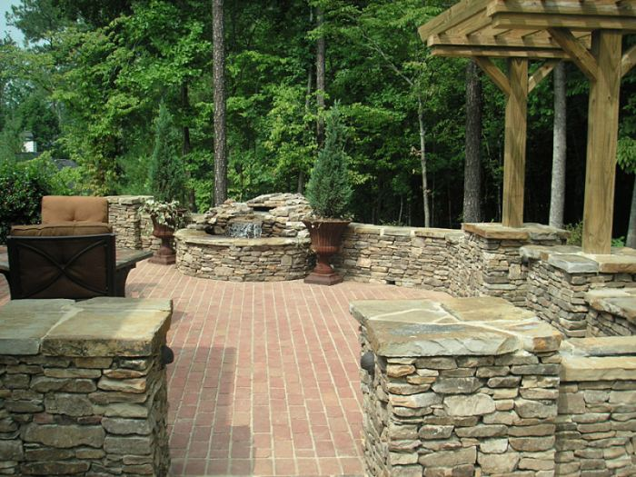 A manufactured brick patio surrounded with natural stone pillars and walls.