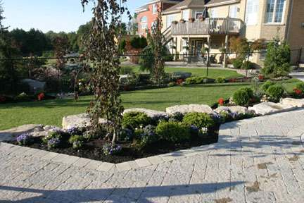Large natural stones support the garden beds as they transition into the raised patio.