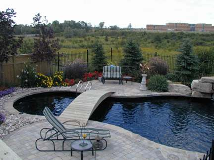 A bridge over the pool leads to a quaint sitting area surrounded by nature.