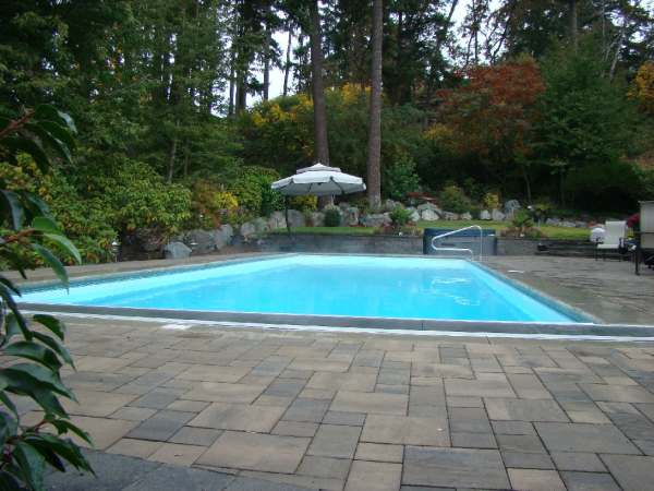 Privacy built from a natural backdrop of green space gives this formal pool area lots of appeal.