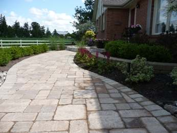 A formal brick walkway leads to the front of this house.