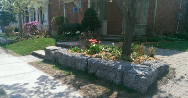 Single large stone blocks are an easy way to make a raised garden bed on a small slope. These stones have tons of character with a weathered facing.